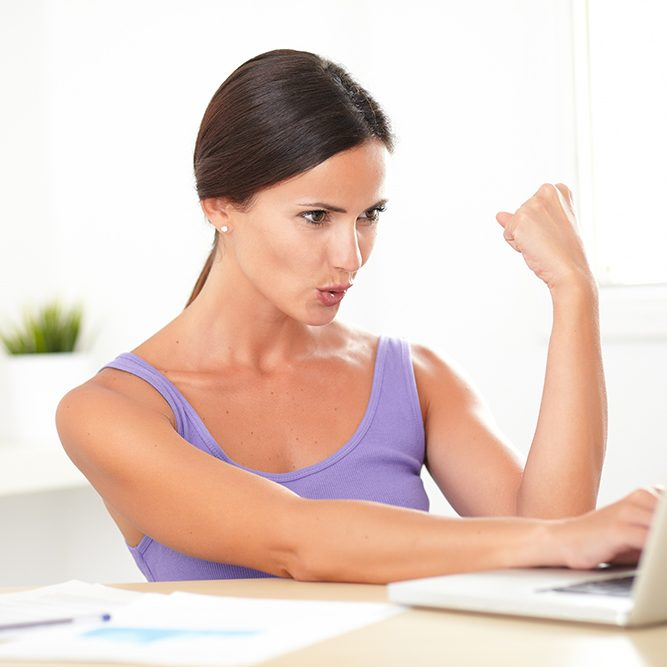 Excited Young Woman Sitting And Working On Laptop